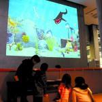 描いた絵が壁の「水族館」に映し出される姿を見て楽しむ子ども