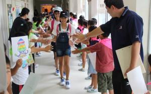 坂の上小児童の歓迎を受ける田中小の子どもたち(中央)