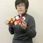 体験教室で作る犬と兜の飾りを持つ担当の塩川由美子さん