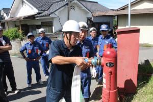 消防団の指導で消火栓にホースを接続する区民(芝生田区)