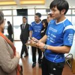 懇親会参加者から求められ色紙にサインする両角友佑選手(写真右)