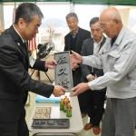 佐久建設事務所の坂下伸弘所長(左)から橋名板を受け取る岸野地区区長会長の木内昌明さん(右)
